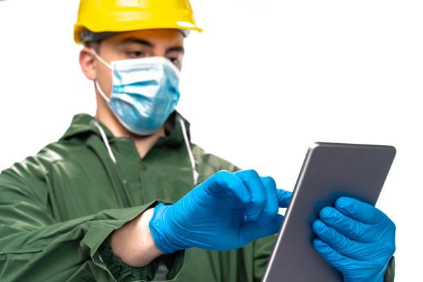 junger ingenieur oder arbeiter mit n95 gesichtsmaske und chirurgischen handschuhen mit digitalem tablet auf weißem hintergrund - ffp2 stock-fotos und bilder