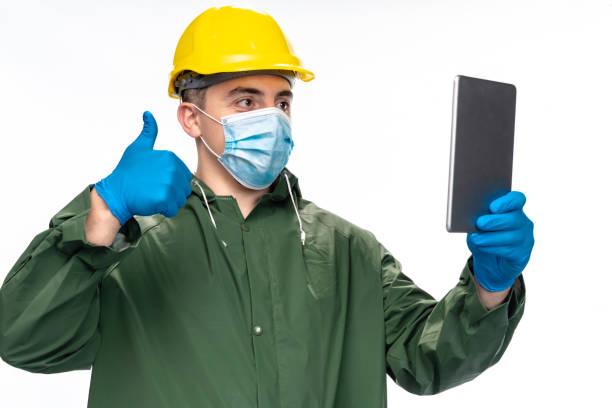 junger ingenieur oder arbeiter mit n95 gesichtsmaske und chirurgischehandschuhen mit digitalen tablet für videoanruf, zeigt daumen nach oben zeichen - ffp2 stock-fotos und bilder