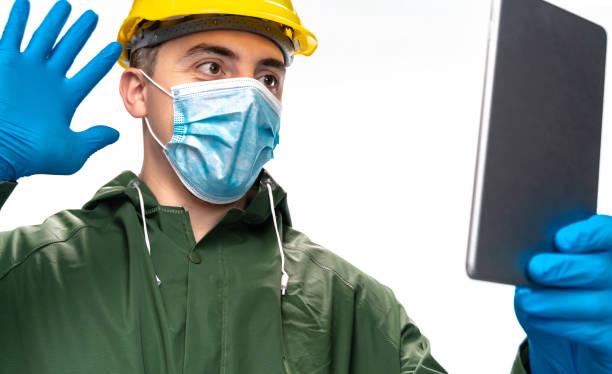junger ingenieur oder arbeiter mit n95 gesichtsmaske und chirurgischehandschuhen mit digitalem tablet für videoanruf auf weißem hintergrund - ffp2 stock-fotos und bilder