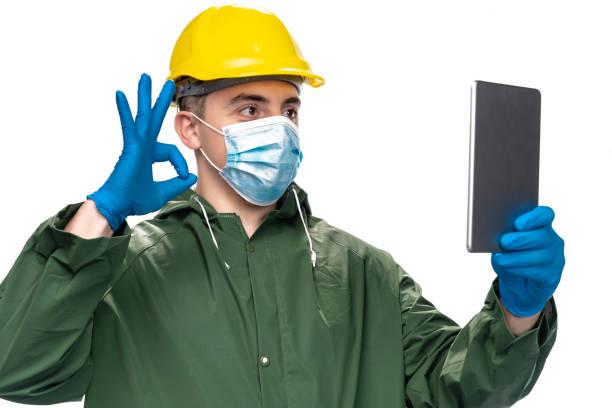 junger ingenieur oder arbeiter mit n95 gesichtsmaske und chirurgischehandschuhen mit digitalen tablet für videoanruf, zeigt ok zeichen - ffp2 stock-fotos und bilder