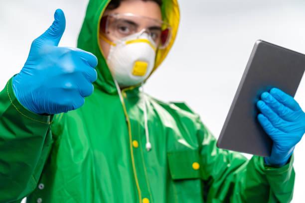 junger ingenieur oder arbeiter mit n95 gesichtsmaske und chirurgischehandschuhen mit digitalem tablet und daumen nach oben zeichen - ffp2 stock-fotos und bilder