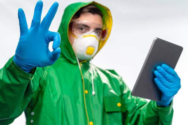 junger ingenieur oder arbeiter mit n95 gesichtsmaske und chirurgischehandschuhen mit digitalen tablet und zeigt ok-zeichen - ffp2 stock-fotos und bilder