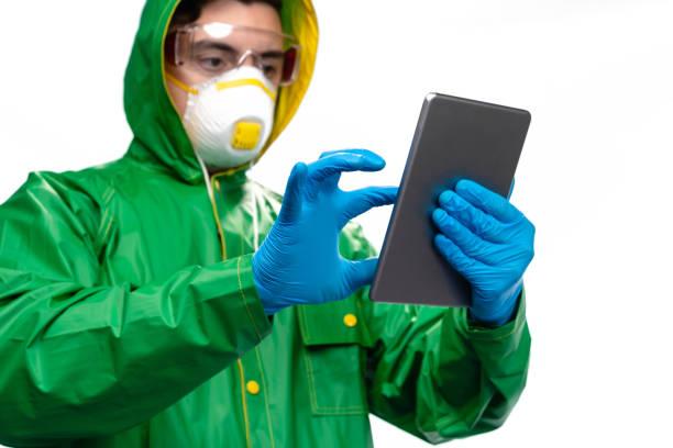 junger ingenieur oder arbeiter mit schützender gesichtsmaske und chirurgischen handschuhen mit digitalem tablet auf weißem hintergrund - ffp2 stock-fotos und bilder
