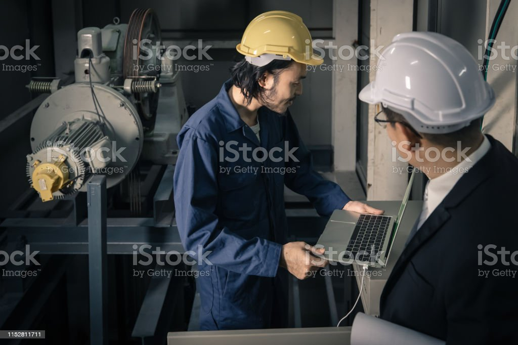 Young Asian engineer use notebook to present his work to senior...