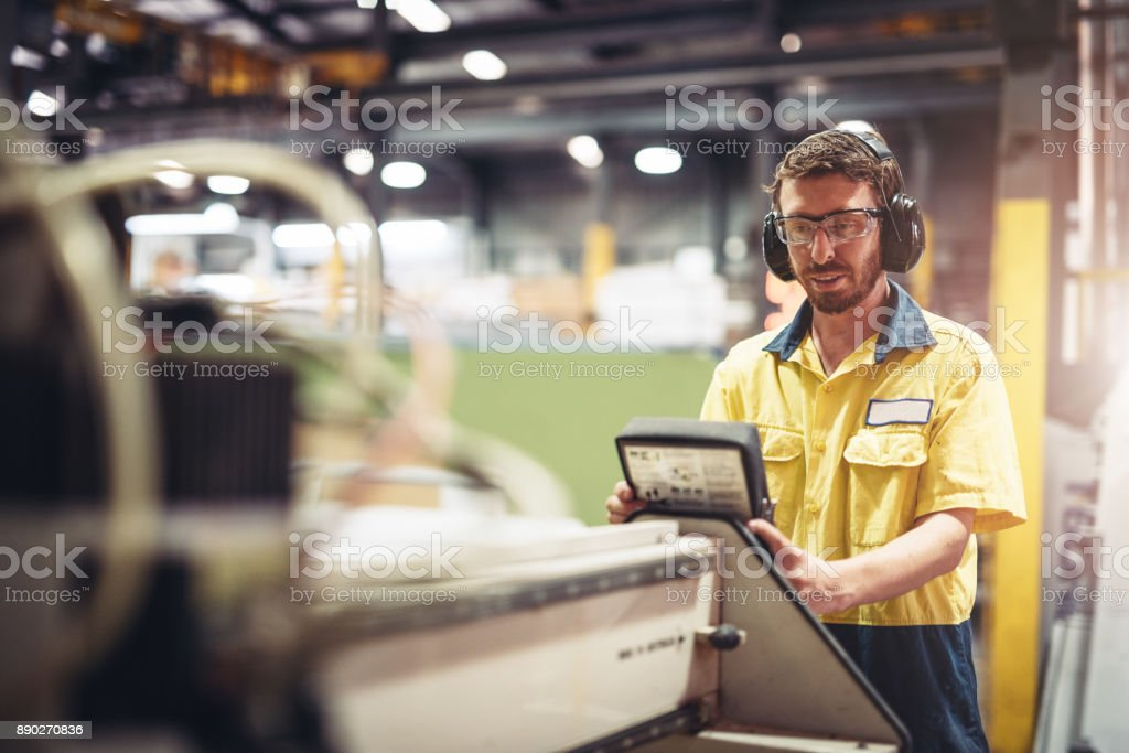 Junger Ingenieur Einrichtung der Produktionslinie Maschinen in australischen produzierenden Unternehmen Lizenzfreies stock-foto