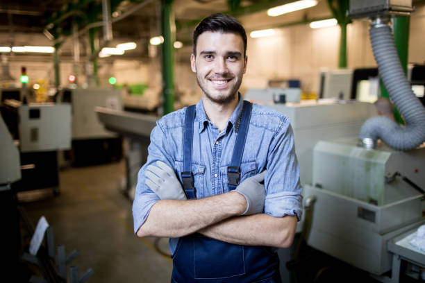 Young engineer standing in factory stock photo