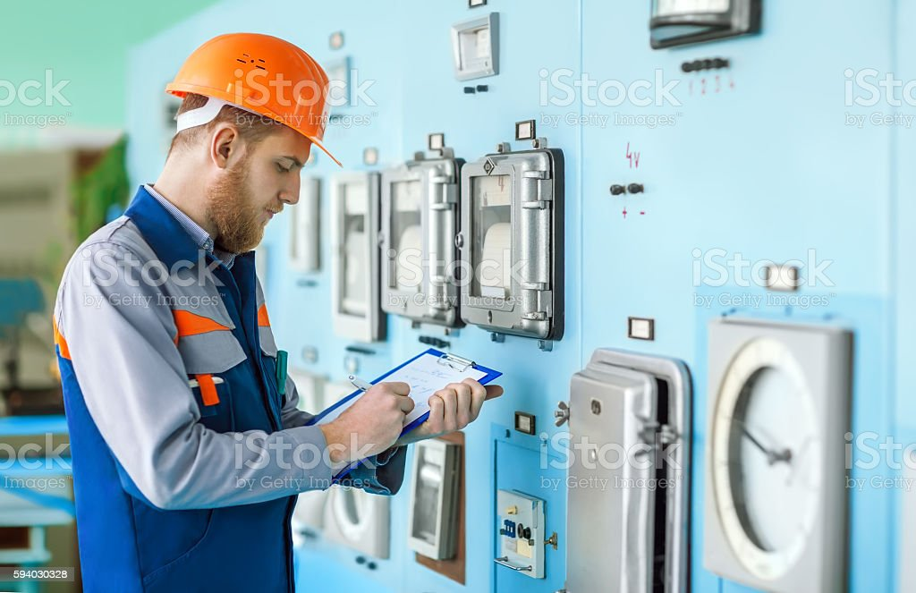 young engineer taking notes at control room stock photo