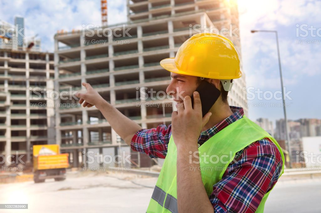 Junge Ingenieur am Bau Website und Kran Hintergrund mit Smartphone sprechen. – Foto