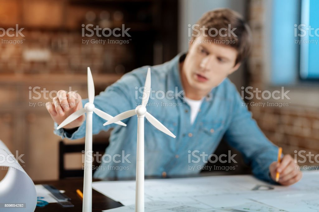 Young engineer touching wind turbine blade stock photo