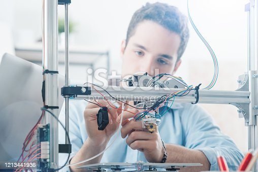 506677574 istock photo Young engineer using a 3D printer 1213441936