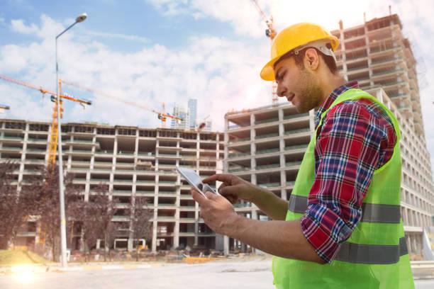 Jung-Ingenieur mit digital-Tablette mit Bau-Website und Kran-Hintergrund. – Foto