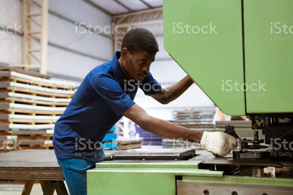 Young engineer using puller machine in industry Male engineer using puller machine at industry. Young apprentice is wearing uniform. He is working in factory. 25-29 Years Stock Photo