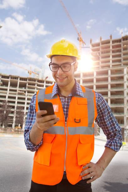 Jung-Ingenieur mit Smartphone auf Bau-Website und Kran-Hintergrund. – Foto
