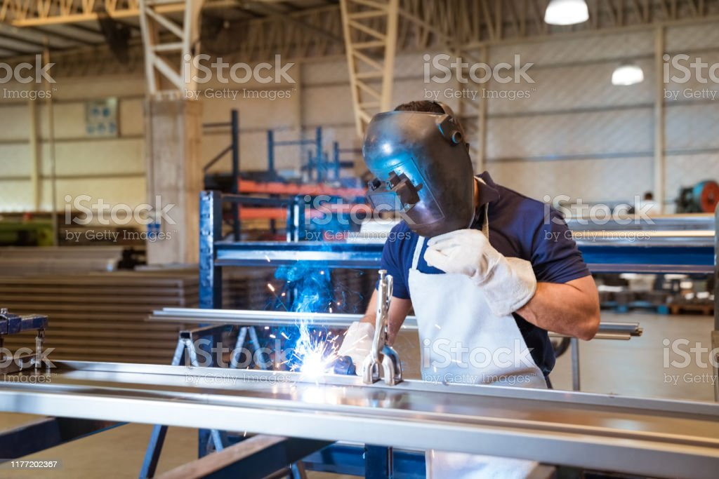 Young engineer welding metallic equipment Male worker welding metallic object. Young engineer is wearing mask while working in manufacturing factory. He is wearing apron. 20-24 Years Stock Photo