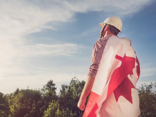 jeune ingénieur, hardhat blanc et drapeau canadien - 1er mai photos et images de collection
