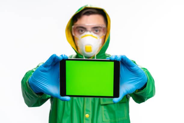 junger ingenieur mit grünem regenmantel, brille und schutzheiner gesichtsmaske mit digitalem tablet mit leerem bildschirm - ffp2 stock-fotos und bilder
