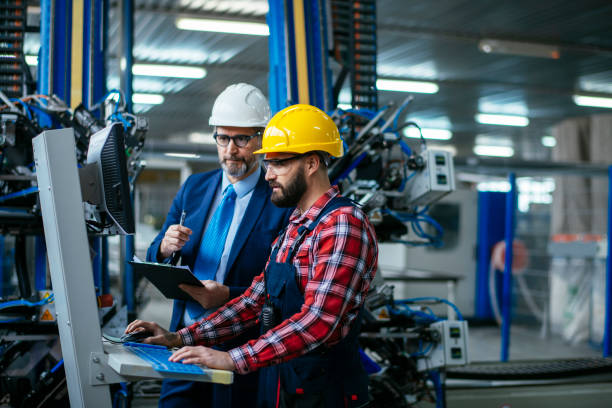 Young engineer with quality control inspector in factory stock photo stock photo