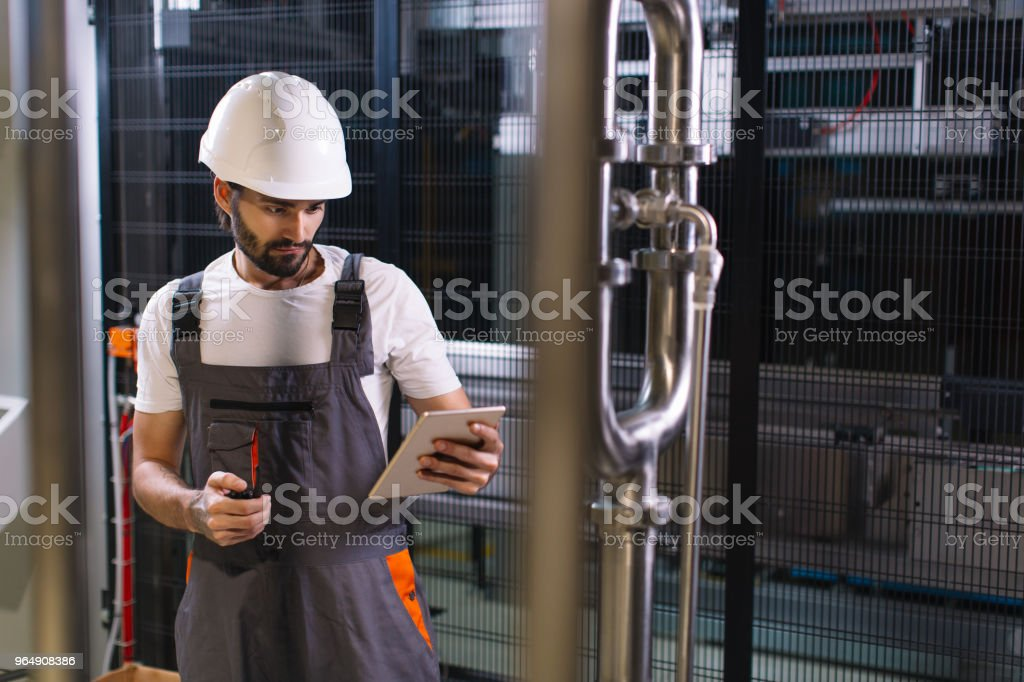 Young engineer with tablet working in factory royalty-free stock photo