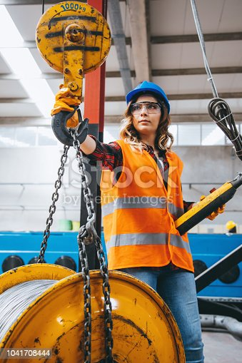 istock Young engineer woman holding and working with remote control for operating crane 1041708444