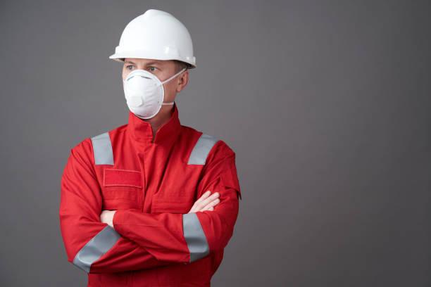 年輕的工程師工人戴頭盔,面罩圖像檔