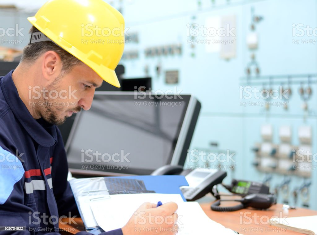 Young engineer working in electrical room in power substation stock photo