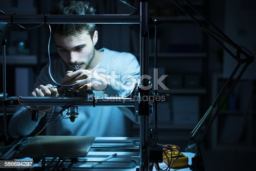 istock Young engineer working on a 3D printer 586694292