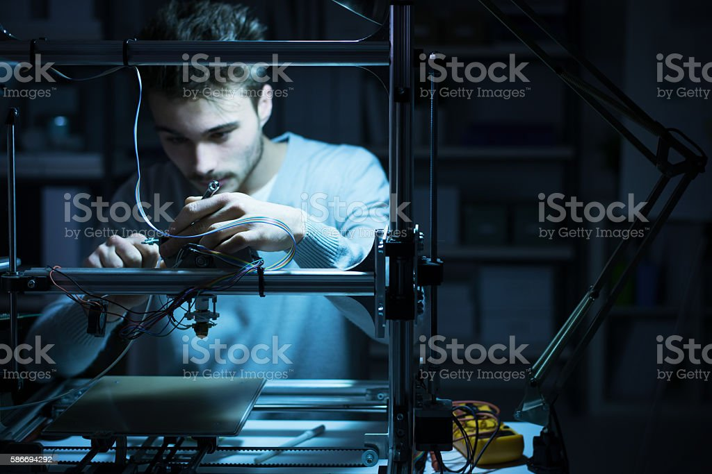 Young engineer working on a 3D printer stock photo