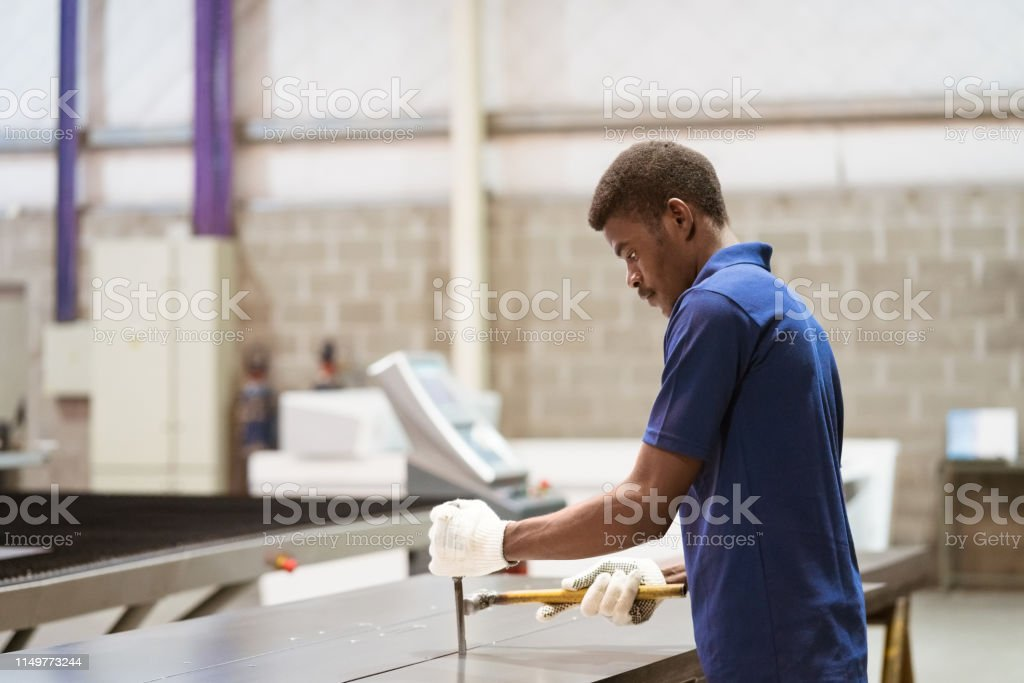 Young engineer working on metal sheet at industry Side view of young engineer working on metal sheet. Male apprentice is hammering machine part. He is standing in industry. 25-29 Years Stock Photo