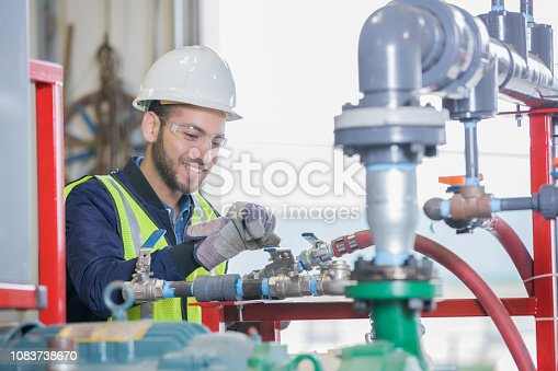 Young adult Hispanic man is working on equipment on pipeline job site for oil and gas company. Engineer is wearing hard hat and observing correct safety procedures.