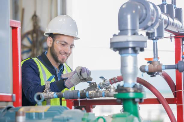 joven ingeniero trabajando en equipo de tubería para petróleo y gas de la empresa - compresor motor fotografías e imágenes de stock