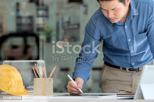 994878714 istock photo Young engineer working with lablet in modern office. 1213678493