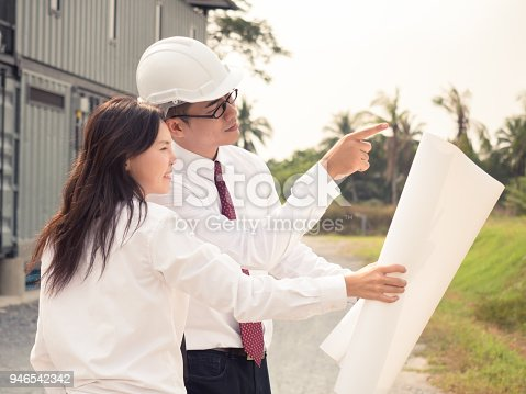 681142982 istock photo Young engineer/architect pointing to construction building plan to customer, hand holding drawing blueprint plan for home/factory 946542342
