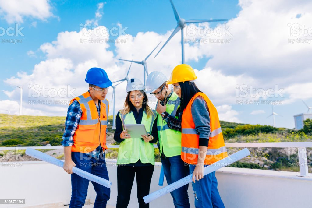 Young engineers and workers having a meeting at wind farm stock photo