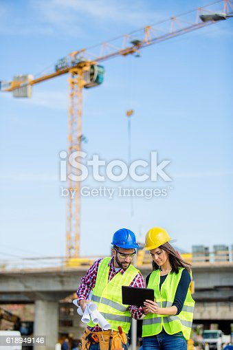 617878058 istock photo Young engineers loking at the papers at the construction site 618949146