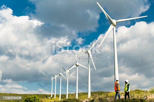 Two young caucasian technician engineer man and woman wearing white worker headwear standing, working, checking farm field system and looking up at wind turbine farm power generation station in rural landscape.