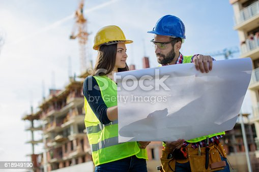 617878058 istock photo Young engineers looking at blueprints 618949190