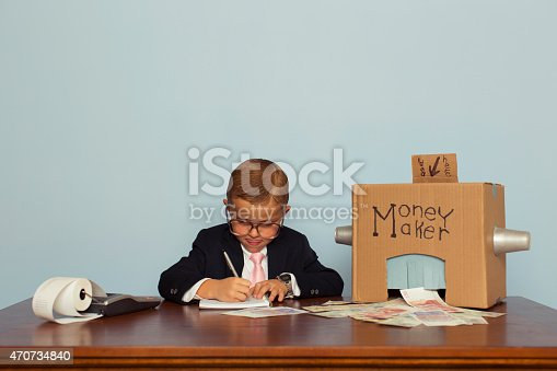 A young boy and businessman works hard to feed his money making machine with great ideas and out comes lots of British Pounds Sterling. Bling. Boy dressed in business suit. Retro styled.