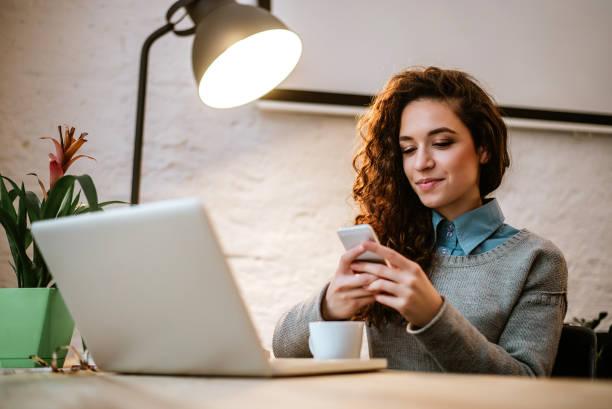 jonge ondernemer op haar werkplek met behulp van de laptop en telefoon. - business woman phone stockfoto's en -beelden