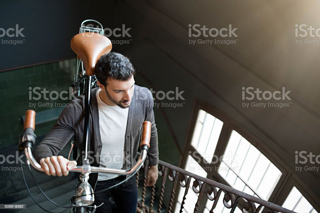 Young entrepreneur businessman arriving in the office carrying his bike stock photo