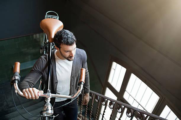 junge unternehmer geschäftsmann, die im büro tragen sein fahrrad - fahrradträger stock-fotos und bilder