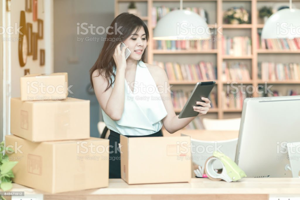 Young entrepreneur checking products stock on the smart tablet while talking to her customer at home office stock photo