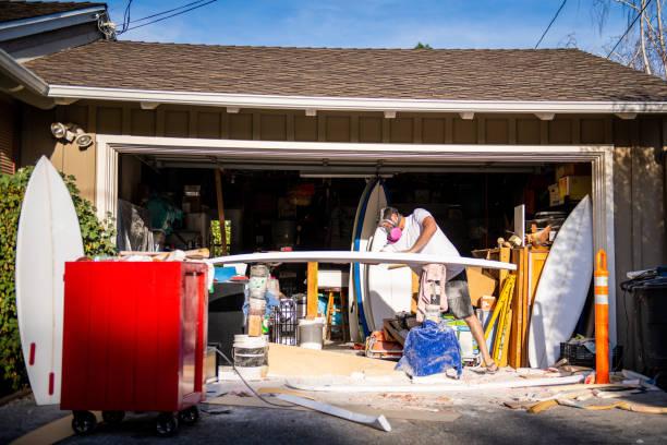 unga entreprenör crafting en anpassad surfbräda i garage studio - surf garage bildbanksfoton och bilder