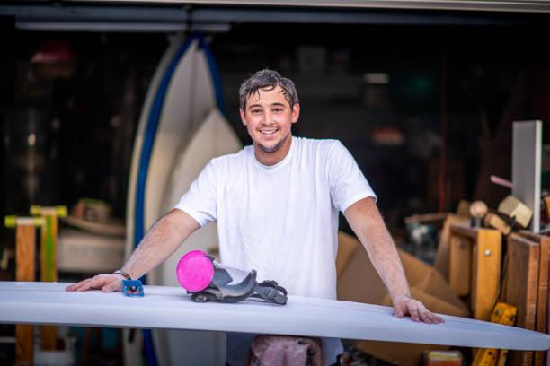 unga entreprenör crafting en anpassad surfbräda - surf garage bildbanksfoton och bilder