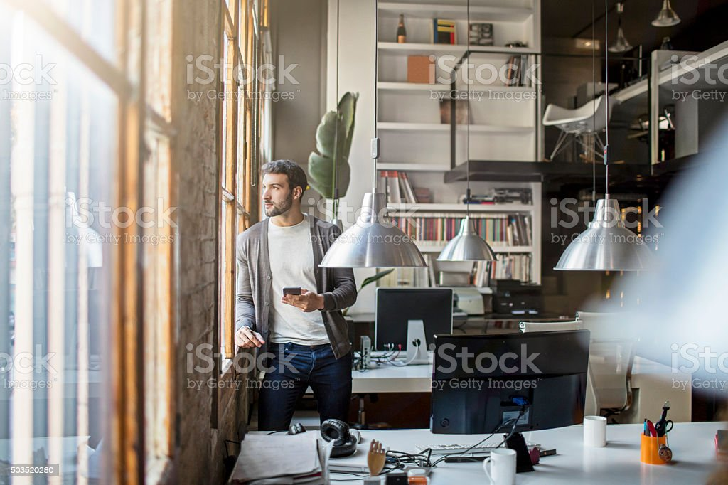 Young entrepreneur looking through the window in the office stock photo