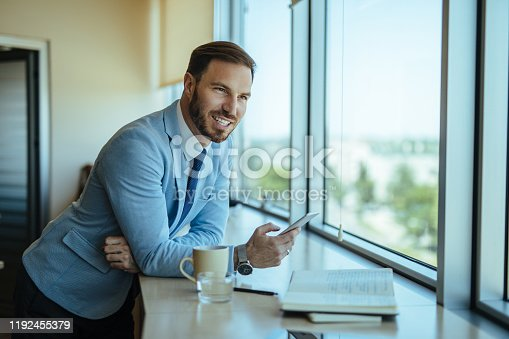 Young entrepreneur looking through the window waiting for a callback from his client