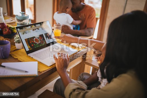 istock Young entrepreneur mother with children blogging online at home 995448754