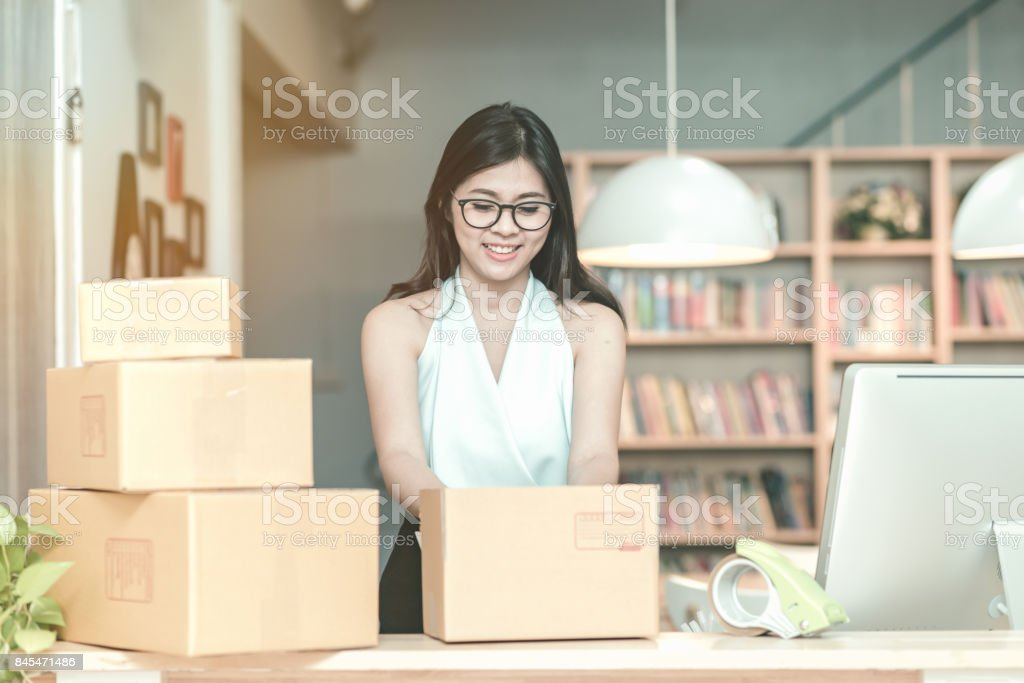 Young entrepreneur packing product into the box for her customers after received order at home office stock photo