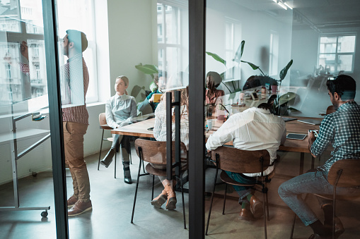 Businessman is writing on the whiteboard. Business people watching a presentation on the whiteboard. Multi-ethnic group of creative people on a business meeting in modern office. Creative team sitting on a conference table in board room. The view is through glass.