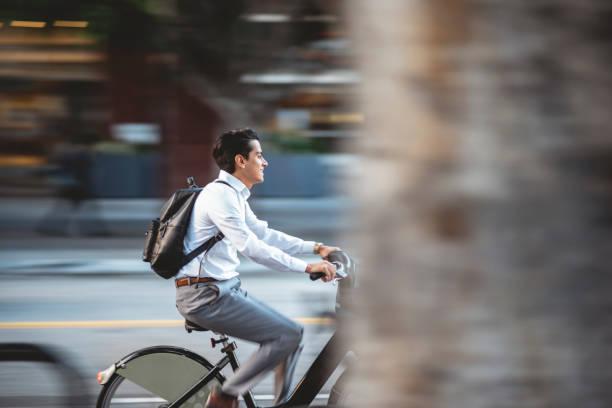 Jungunternehmer fährt Fahrrad in der Stadt – Foto
