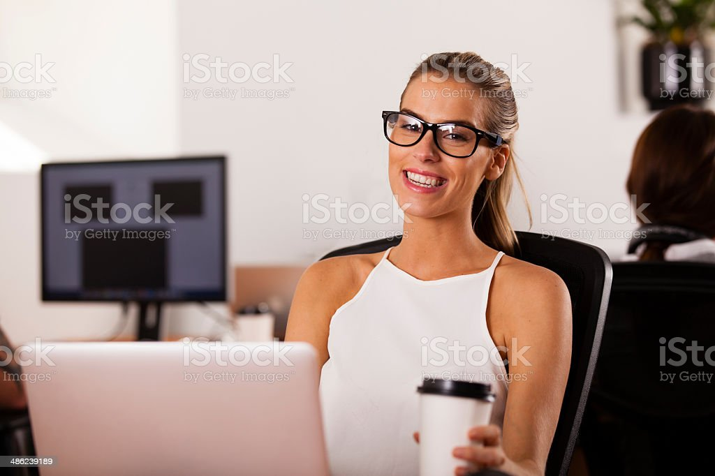 Young entrepreneur smiling in her startup office stock photo